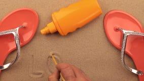 Ame, inscripción escrita a mano en la arena, entre los accesorios de la playa Reconstrucción de la muestra y del símbolo almacen de video