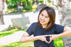Ame la muestra adolescente asiática del corazón de la mano de la demostración del concepto sano Foto de archivo libre de regalías