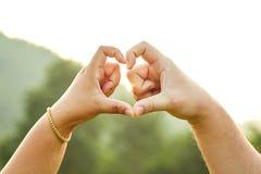 Ame la muestra de la mano con forma del corazón con el fondo natural Imagen de archivo