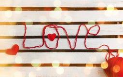 Ame la palabra formada con hilo para obras de punto rojo en fondo de madera Imagenes de archivo