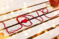 Ame la palabra formada con hilo para obras de punto rojo en fondo de madera Imágenes de archivo libres de regalías