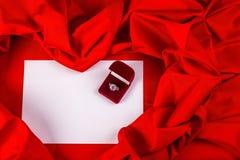 Ame la tarjeta con el anillo de diamante en una tela roja Fotos de archivo libres de regalías