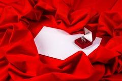 Ame la tarjeta con el anillo de diamante en una tela roja Fotografía de archivo libre de regalías