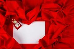 Ame la tarjeta con el anillo de diamante en una tela roja Imágenes de archivo libres de regalías