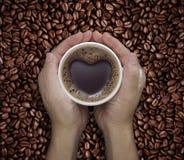 Ame la taza de café en manos con forma del corazón en haba Fotos de archivo