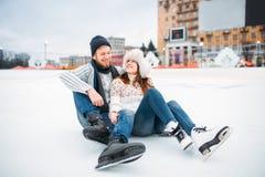 Ame los pares en los patines que se sientan en el hielo, pista de patinaje Foto de archivo libre de regalías