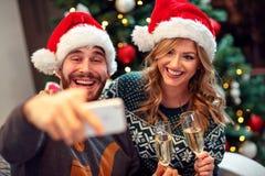 Ame los pares que se divierten y tome las imágenes de la Navidad en móvil imagen de archivo libre de regalías