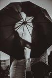 Ame na chuva/silhueta de pares de beijo sob o guarda-chuva Foto de Stock