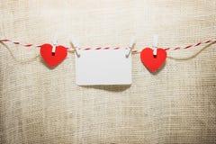 Ame o cabo natural dos corações do Valentim e a suspensão vermelha dos grampos Imagens de Stock Royalty Free