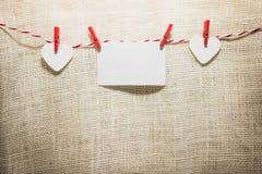Ame o cabo natural dos corações do Valentim e a suspensão vermelha dos grampos Fotos de Stock