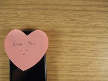 Ame-o com escrita de sorriso da cara na nota da etiqueta e telefone celular preto no fundo de madeira Imagens de Stock Royalty Free