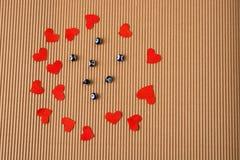 Ame o conceito com corações e os grânulos de papel vermelhos Foto de Stock Royalty Free
