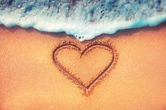 Ame o coração em uma areia da praia com a onda no fundo Imagens de Stock