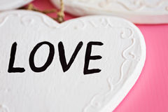 Ame o coração branco de madeira no fundo cor-de-rosa, compositi horizontal Fotos de Stock