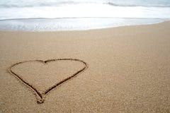 Ame o coração tirado na areia em uma praia Fotografia de Stock