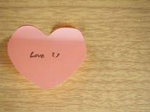 Ame-o, escrevendo na nota pegajosa, forma do coração no fundo de madeira Foto de Stock Royalty Free