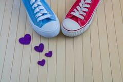 Ame o fundo com sapatilhas diferentes e corações roxos Fotografia de Stock Royalty Free