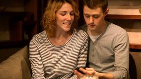 Ame o indivíduo e a menina que sentam-se na tabela, telefone celular em um café video estoque