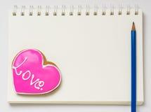 Ame o livro da placa do livro de nota do diário com lápis O coração deu forma à cookie em uma página vazia do diário fotografia de stock royalty free