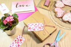 Ame o presente, a begônia, os cartões e as cookies na tabela de madeira Fotos de Stock Royalty Free