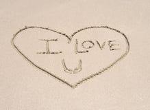 Ame o símbolo do coração na areia na praia tropical Imagem de Stock