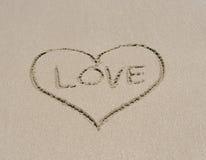 Ame o símbolo do coração na areia na praia tropical Imagens de Stock Royalty Free