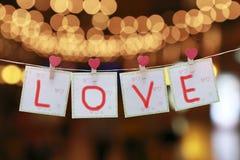 Ame o símbolo e os corações que penduram na corda Imagem de Stock