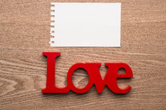 Ame o símbolo escrito na letra de madeira com cartão da mensagem Foto de Stock