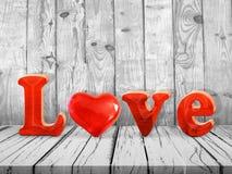 Ame o sinal com coração de vidro vermelho na tabela de madeira Foto de Stock