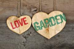 Ame o sinal de madeira do coração da mensagem do jardim no fundo cinzento áspero Fotografia de Stock