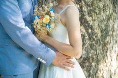 Ame os pares do casamento, ramalhete do casamento nas mãos dos noivos Foto de Stock Royalty Free
