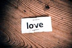 Ame a palavra escrita no papel rasgado e grampeado imagem de stock
