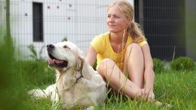 Ame para animais de estimação - uma mulher loura nova que descansa com seu cão na grama video estoque