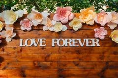 Ame para siempre las muestras en el tablero de madera adornado por las flores Fotos de archivo libres de regalías