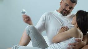 Ame pares na cama que escolhe o preservativo, prevenção da infecção do sexo seguro, controlo da natalidade vídeos de arquivo