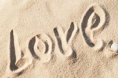 Ame, redacte - escrito a mano en arena en una playa del mar Imágenes de archivo libres de regalías
