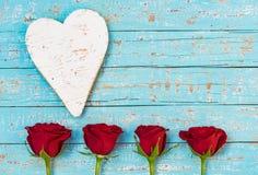 Ame rosas vermelhas e coração das flores no fundo da madeira de turquesa foto de stock