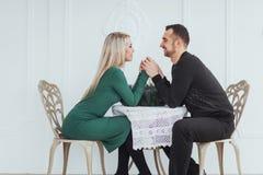 Ame sentar-se no homem e na mulher dos pares da tabela com os copos de vinho no fundo branco no restaurante Jantar dos Valentim Foto de Stock Royalty Free