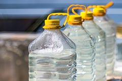 Ameaças da falta e das alterações climáticas da fonte de água Garrafas plásticas enchidas com a agua potável fotografia de stock royalty free