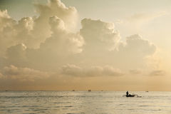 Amed, Bali, Indonesia. A Balinese fishing boat, called a Jukung, heads out to sea for a morning of fishing for mackerel under an imposing stormy sky Stock Photos