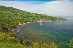 Amed, Bali, Indonesia. Amed has become a popular tourist destination and is located on the east coast of Bali. Here a sailboat leaves the calm waters of this Stock Images