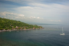 Amed, Bali, Indonesia. Amed has become a popular tourist destination and is located on the east coast of Bali. Here a sailboat leaves the calm waters of this Stock Image