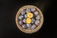 Ameixa doce fresca na cesta de vime rústica redonda no chalkboa preto Imagem de Stock