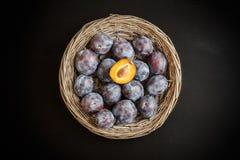 Ameixa doce fresca na cesta de vime rústica redonda no chalkboa preto Imagem de Stock Royalty Free