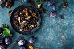 Ameixa seca secada e ameixas frescas com folhas foto de stock