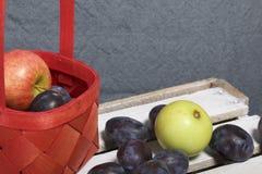 Ameixas e maçãs aromáticas maduras em uma cesta de vime Localizado em uma caixa de madeira, batida fora das placas fotos de stock