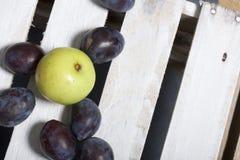 Ameixas e maçãs aromáticas maduras Localizado em uma caixa de madeira, batida fora das placas fotos de stock