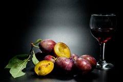 Ameixas maduras e close-up suculento do tiro em um fundo escuro e em um vidro do vinho imagem de stock royalty free