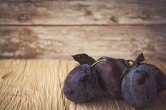 Ameixas maduras em um fundo de madeira Foto de Stock Royalty Free