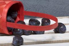 Ameixas perfumadas maduras em uma cesta de vime Localizado em uma caixa de madeira, batida fora das placas fotografia de stock royalty free
